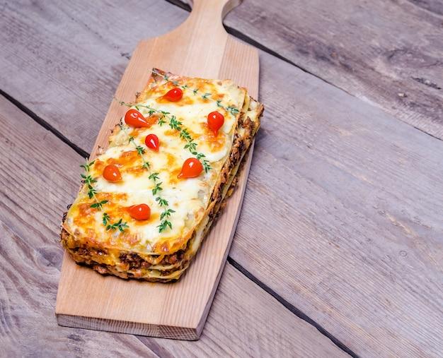 Gedeelte van lasagne op de houten tafel
