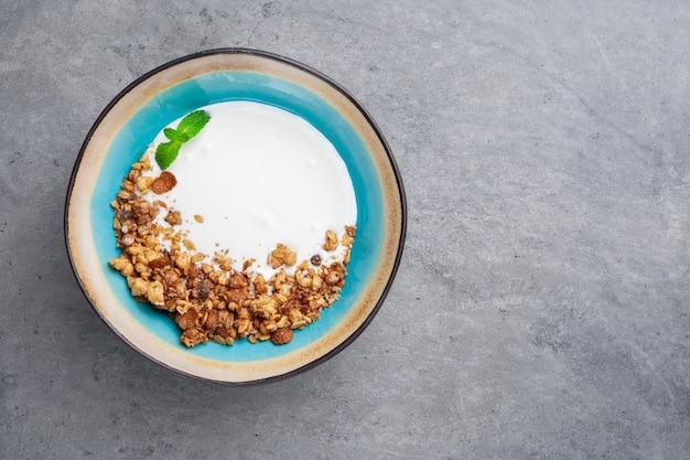 Gedeelte van natuurlijke yoghurt met zelfgemaakte granen granola in blauwe kom