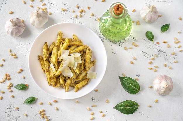 Gedeelte van pesto penne pasta met ingrediënten op de witte houten tafel