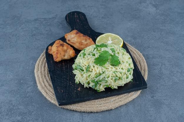 Gedeelte van rijst met kipnuggets op zwart bord.