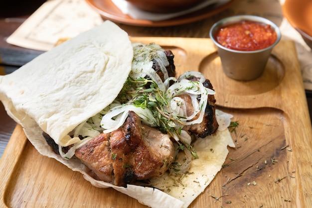 Gedeelte van sappige kebabs met uien op een houten dienblad met pitabroodje en saus