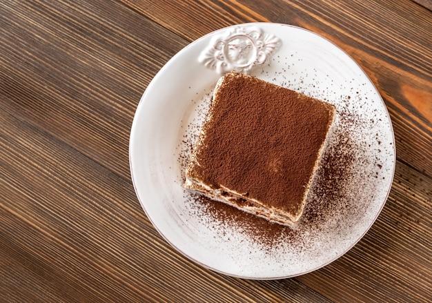 Gedeelte van tiramisu italiaans dessert op houten achtergrond