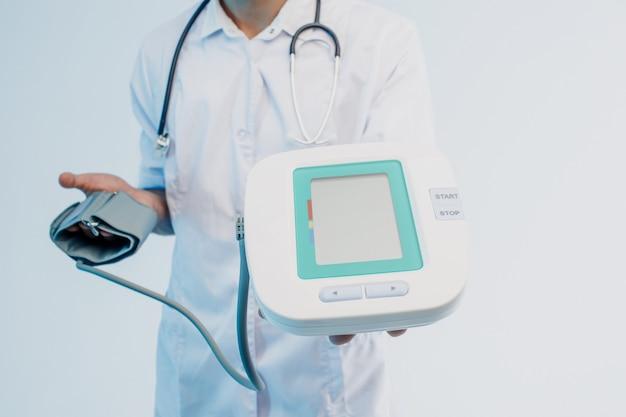 Gedeeltelijk beeld van mannelijke arts die digitale tonometer toont. man met een stethoscoop die een witte jas draagt. geïsoleerd op een grijze achtergrond met turkoois licht. studio opname. ruimte kopiëren