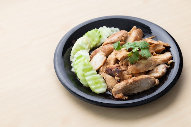 Gedeeltelijk gesneden gegrilde kipfilet met komkommer in zwarte plaat op houten tafel.