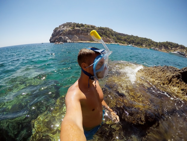 Gedeeltelijk wazig beeld door waterdruppels. jonge mannelijke ontdekkingsreiziger in avontuur klaar om te snorkelen. selfie geschoten op een zomerdag op een rots in het midden van de zee.