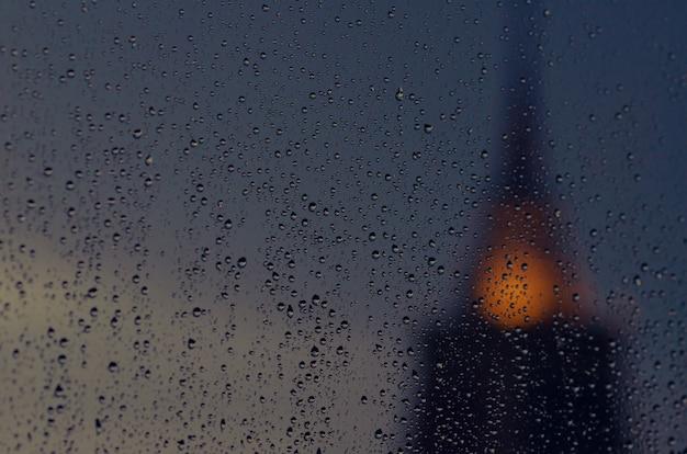 Gedeeltelijke nadruk van regendaling op glasvenster in moessonseizoen met vage pagode van tempelachtergrond.