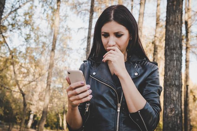 Gedeeltelijke weergave van brunette vrouw in jas met smartphone in herfstbos. wandelend in het park meisje leest haar mobiel en raakte in de war als ze slecht nieuws kreeg. vrouwelijke bedrijf telefoon op de achtergrond van de natuur.