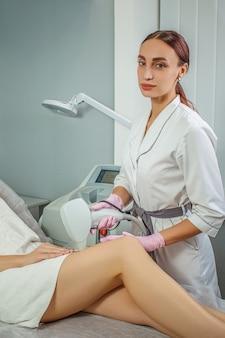 Gedeeltelijke weergave van jonge vrouw laser ontharing epilatie op dij ontvangen