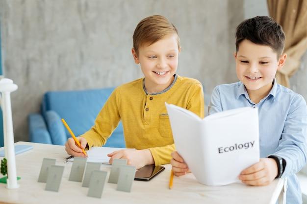 Gedegen studenten. ijverige pre-tienerjongens die aan tafel zitten en het boek voor de ecologieles bestuderen terwijl ze aangenaam glimlachen