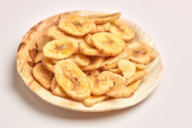 Gedehydrateerde banaan in houten plaat geïsoleerd op een witte achtergrond.
