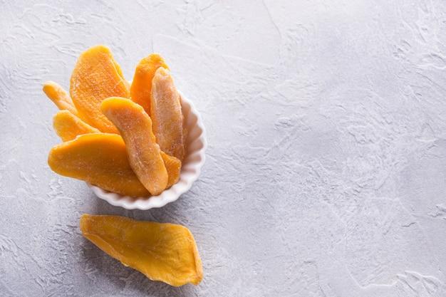 Gedehydrateerde en gedroogde mango chips in witte kom close-up