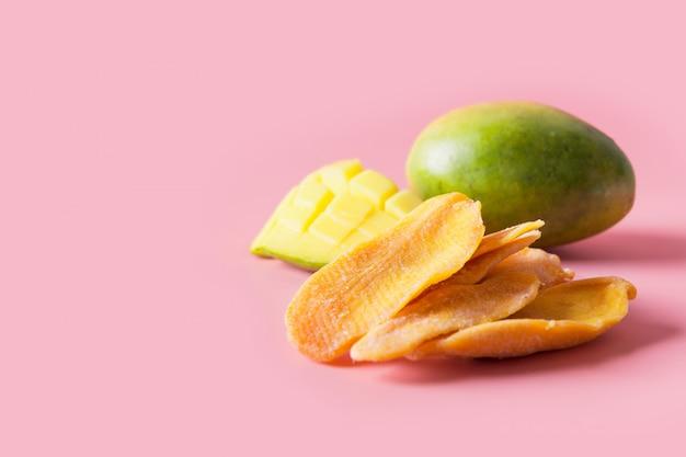 Gedehydrateerde en gedroogde mango chips op roze close-up