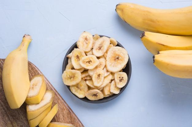Gedehydrateerde, gedroogde bananenchips op lichte achtergrond. uitzicht van boven.