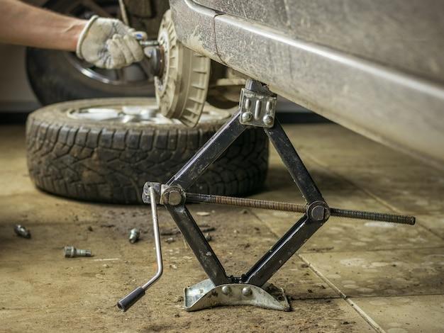 Gedemonteerde auto op een krik in de garage.