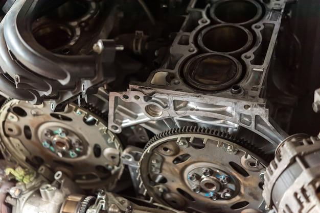 Gedemonteerde auto vuile motor en katrol bij garage