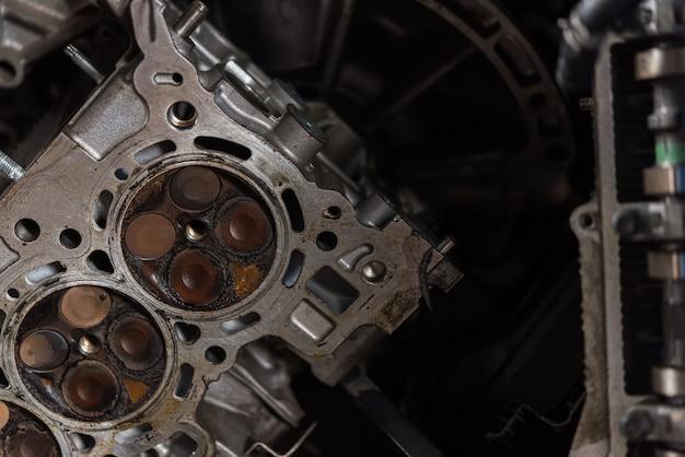 Gedemonteerde cilinder van de auto de vuile motor bij garage