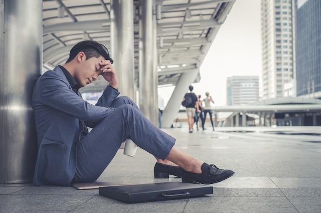 Gedeprimeerde en vermoeide zakenmanzitting bij stad