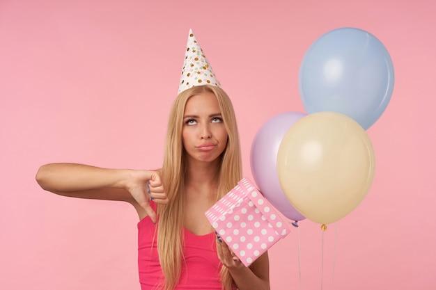 Gedesillusioneerde langharige blonde vrouw met ongedwongen showen met haar duim en rollende ogen teleurgesteld, verjaardag viert met veelkleurige luchtballonnen, geïsoleerd op roze achtergrond