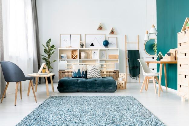 Gedessineerd tapijt in de buurt van fauteuil en smaragdgroene matras in kleurrijk woonkamerinterieur met stoel