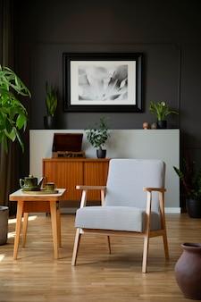 Gedessineerde fauteuil naast houten tafel in donkergrijs woonkamer interieur met poster. echte foto