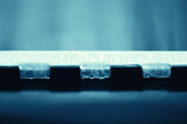 Gedetailleerde achtergrond van fragment van automobielradiator in macro met exemplaarruimte. zwart-wit beeld van metalen auto-onderdeel is close-up. lege oppervlakte van staaltextuur in blauwe toon.