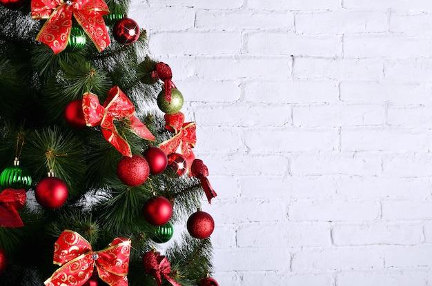 Gedetailleerde foto van de kerstboom op witte bakstenen muur