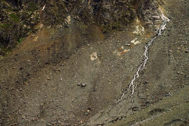 Gedetailleerde natuurlijke textuur van helling van losse stenen. bergwater stroom stroomt langs berghelling. kleine waterval op rots. ongewoon landschap van majestueuze natuur.