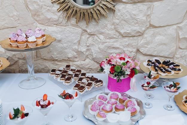 Gediende bartafel van een verscheidenheid aan snoepjes zoals tiramisu, eclairs en cupcakes