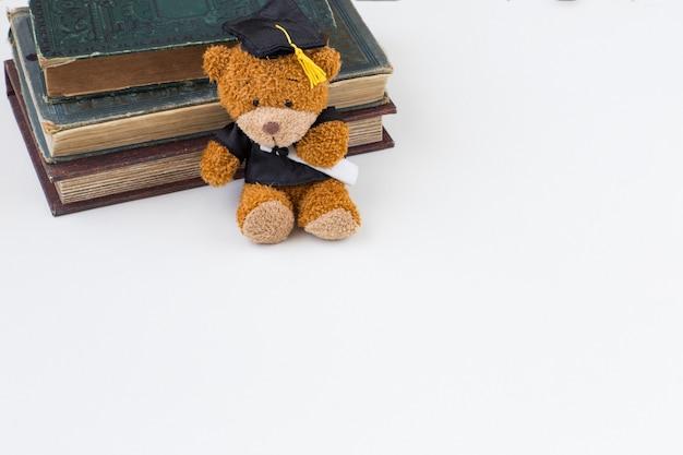 Gediplomeerd in een gediplomeerde pet en oude boeken op een witte achtergrond