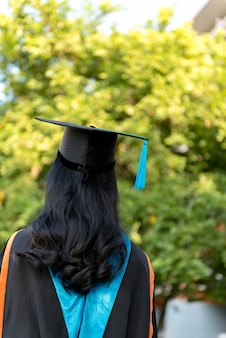Gediplomeerd jong meisje dat een zwarte leeswijzerhoed draagt.