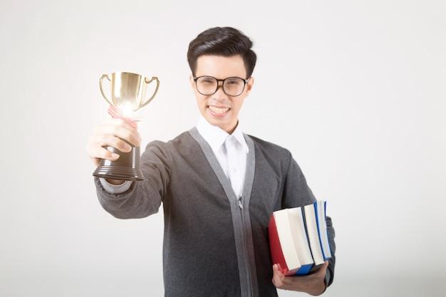 Gediplomeerde die gouden trofee houdt. studio die op witte achtergrond is ontsproten. concept voor onderwijs