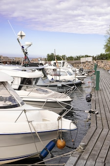 Gedokte boten. afgemeerde boten. boten die zich op een rij bij een houten pijler bevinden.