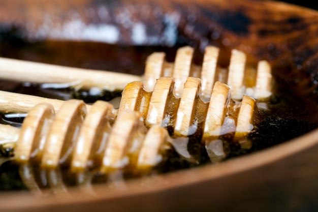 Gedompeld in honing speciaal gemaakt van hout, een zelfgemaakte ruwe lepel, zoete bijenhoning en drie houten lepels waarmee je honing kunt overbrengen en gieten zonder te druppelen en te verspreiden