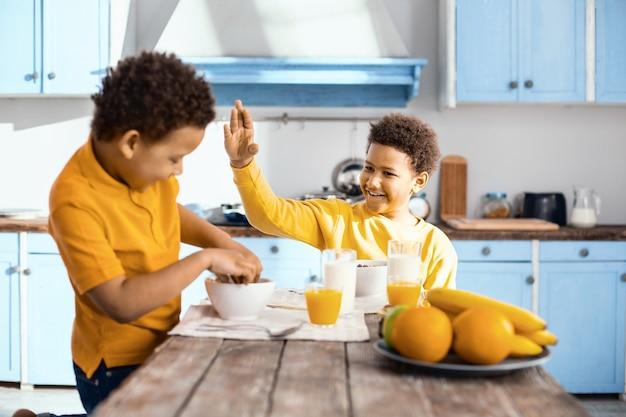 Gedraag je. glimlachende pre-tienerjongen die aan de tafel zit en zijn hand roert alsof hij zijn kleine broertje wil slaan terwijl hij granen eet met zijn handen