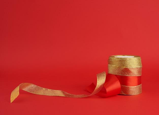 Gedraaid gouden en rood zijdeglanzend lint op rood