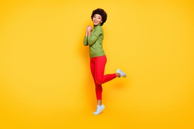 Gedraaid volledige lengte lichaamsgrootte portret van vrolijke positieve schattig vrij aardig meisje in rode broek trendy glimlachend toothily in witte schoeisel.