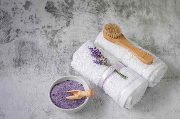 Gedraaide badhanddoeken met badzout en penseel op lichtgrijs. kuuroordhanddoek en reeks badkamerstoebehoren tegen een geweven muur. minimalisme, zachte focus. spa.