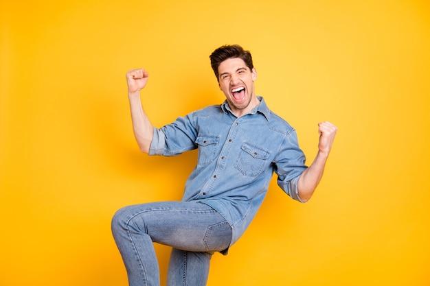 Gedraaide foto van gekke extatische opgewonden dolblij man schreeuwen schreeuwen springen vuisten maken geïsoleerd levendige kleuren muur