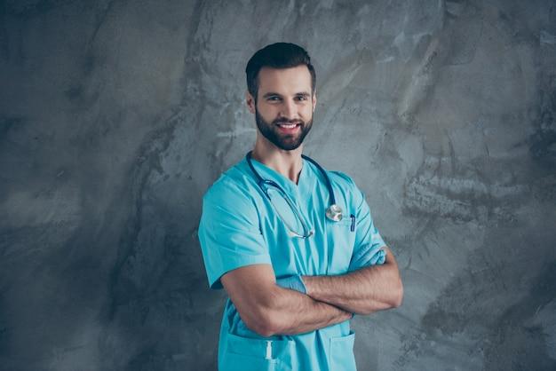 Gedraaide foto van positieve bruinharige vrolijke toothy stralende intelligente man met handschoenen met haren geïsoleerd grijze muur betonnen kleur muur
