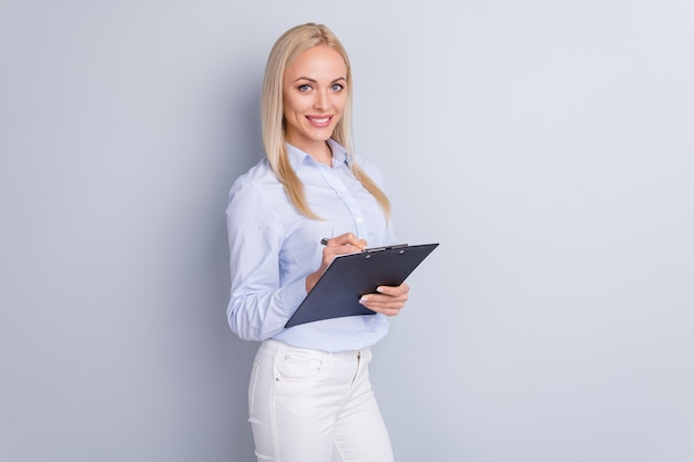 Gedraaide foto van slimme succesvolle assistent-klembord van de meisjesgreep