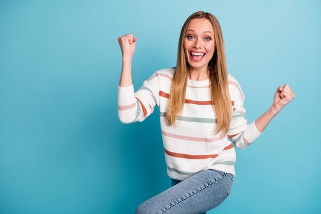 Gedraaide foto van vrolijke trendy blanke vrouw glimlachend toothily vreugde in het hebben gewonnen loterij vuisten dragen jeans denim geïsoleerde pastel blauwe kleur muur