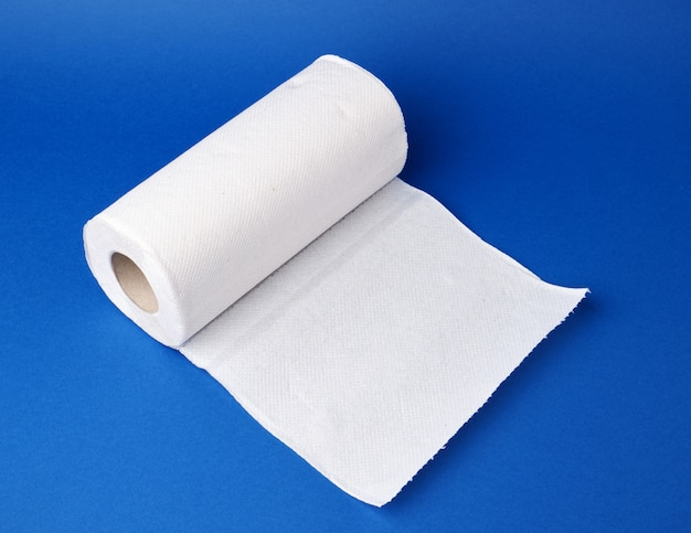 Gedraaide rol witte papieren handdoek op een blauwe ondergrond