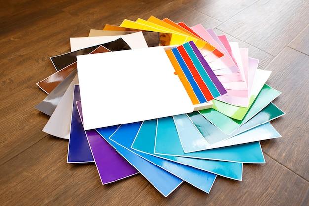 Gedraaide stapel kleurrijke 12x12 vellen zelfklevend papier geïsoleerd op de witte achtergrond. gesorteerde kleuren.