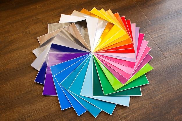Gedraaide stapel kleurrijke 12x12 vellen zelfklevend papier op bruine achtergrond. veel gekleurd papier.
