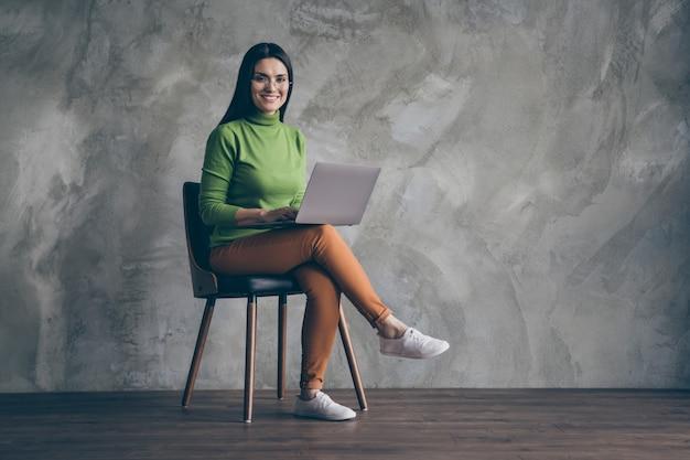 Gedraaide volledige lengte lichaamsgrootte foto van vrolijke vriendin zittend in stoel werken met laptop zelfverzekerd nieuw project ontwikkelen om geïsoleerde grijze muur kleur concrete achtergrond te presenteren