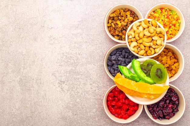 Gedroogd en gekonfijt fruit en cashewnoten in keramische kommen