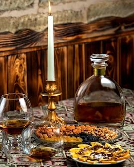 Gedroogd fruit bord met amandel, rozijnen, walnoot geserveerd met sterke drank