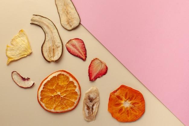 Gedroogd fruit chips op een roze ondergrond