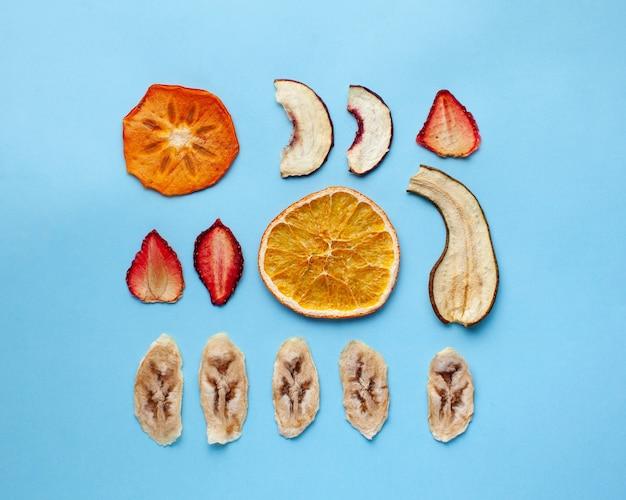 Gedroogd fruit chips van banaan, sinaasappel en anderen op een blauw oppervlak