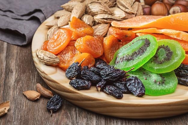 Gedroogd fruit en noten. stilleven op een ronde houten plank.